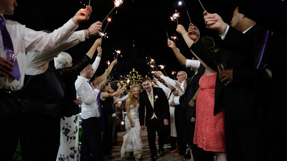 Happy Married Couple with Wedding Guest Holding Sparkler Beside